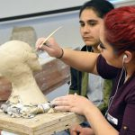 Student working on bust sculpture