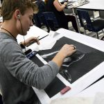 Student drawing on black paper