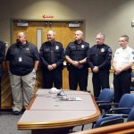 Police officers stand to be recognized during board meeting