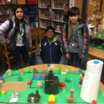 Three students stand behind model prototype city