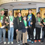 Junior high students stand with trophies and medals