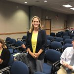 Carrie Johnson stands at board meeting